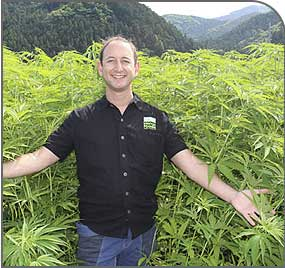Paul Benhaim stands in a field of industrial hemp